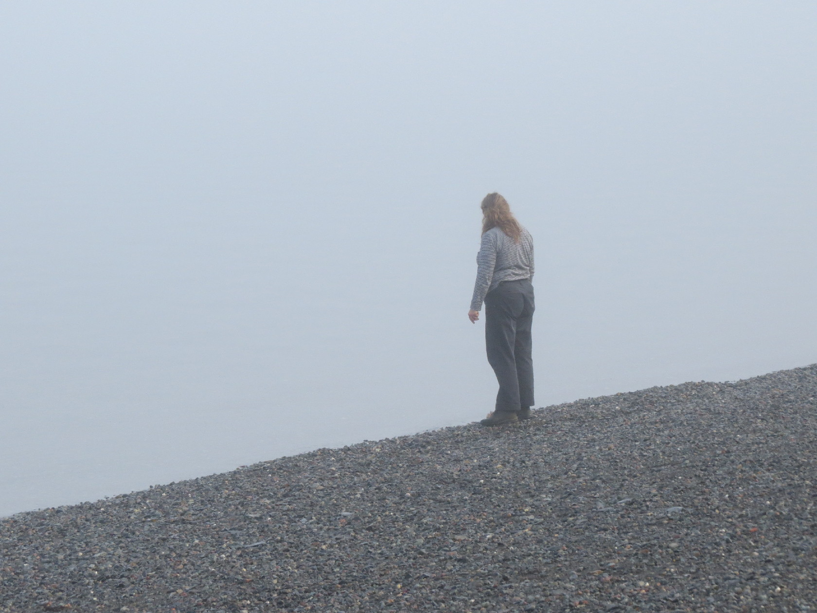 A woman looking into the fog expecting Deer Island ferry, Campobello