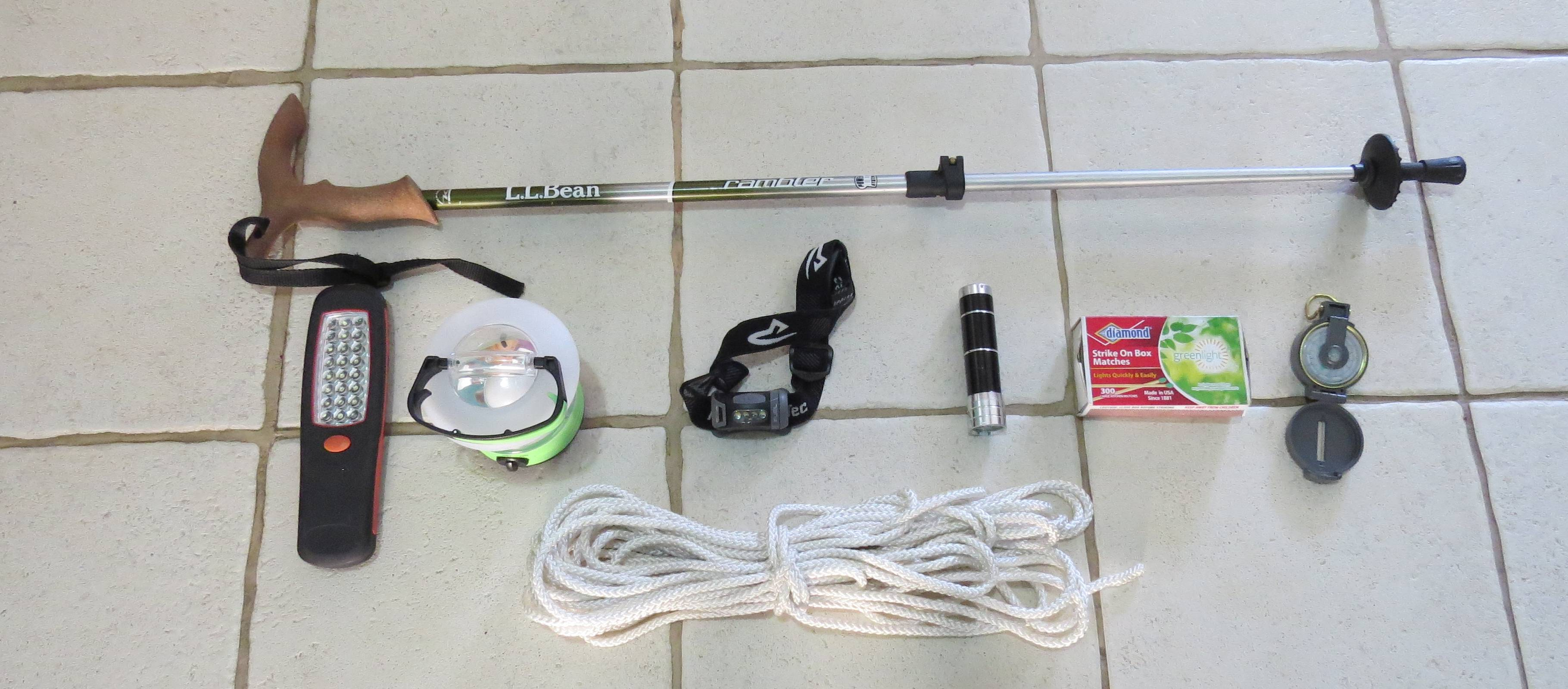 Preparing for a camping trip -gadgets influding flashlights, rope, compass and walking stick