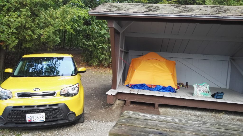 Tent in leanto at Draper's Acres Campground, NYS, with yellow Kia Soul