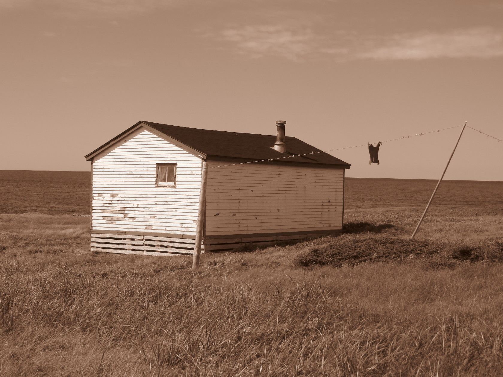 Forlorn house in Broom's Point, sepia with shirt on line, Gros Morne coast
