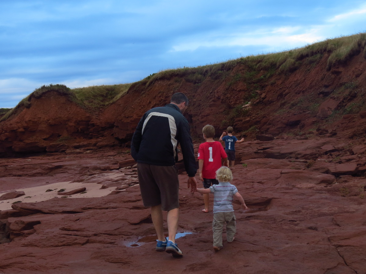 Family walking on red beach. Campbell's Cove, PEI