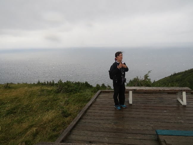 Chinese woman in wind and rain, Skyline, Cape Breton, NS