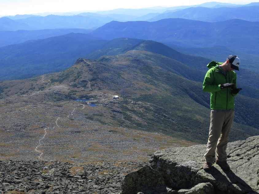 Climber checking cell phone. Vista over mountain refuge, Mount Washington