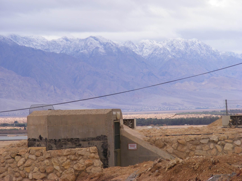 Kibbutz bunker against snowy Edom mountains, Arava 2013