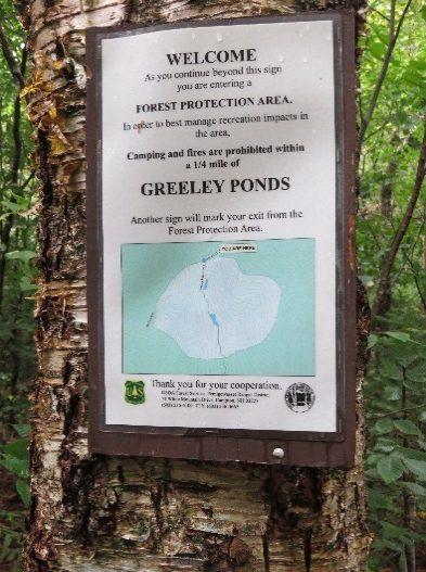 A sign marking Greeley Ponds Trailhead