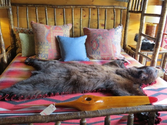 Stuffed bear sprawled over bed in Keene's Furniture Store
