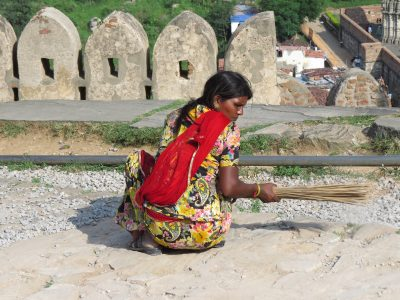 Female cleaner working on road improvement project on way to Kumbhalgarh Fort, Rajasthan