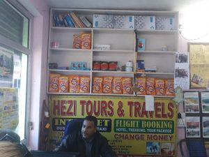 Legendary Hezi sitting at his agency with Israeli products on the shelves, Bhagsu, Himachal Pradesh