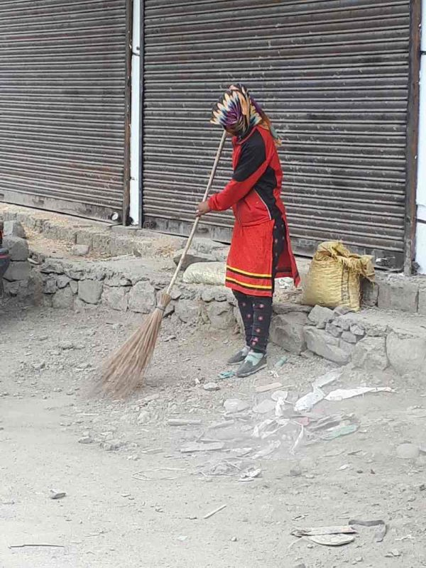 Ladhaki woman cleaning street in Leh, Ladakh