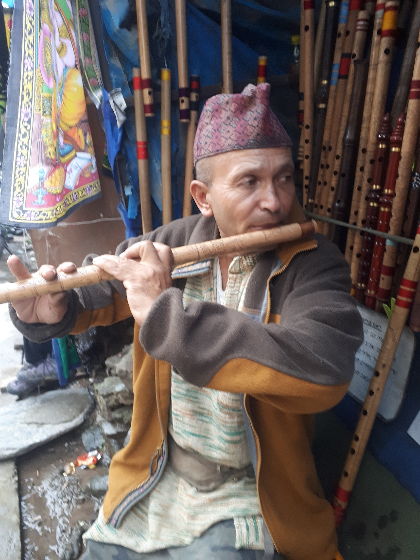 Nepali flute player, teacher and seller playing my future flute on main street, McLoed Ganj