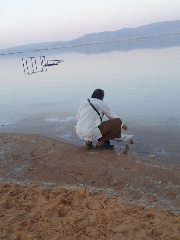 Ananda Das breaking a salt crystal. Dead Sea