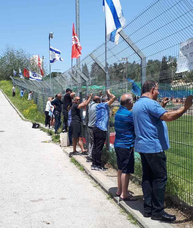 Men watching a neighborhood soccer game on Shabbat morning. Kiryat Yovel, Jerusalem
