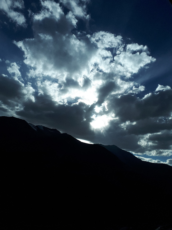 Clouds, sun, mountain on road to Leh