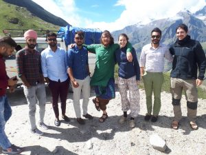 Our group and other travelers posing against snowy peaks on road from Manali to Leh