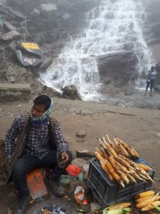 Bram and Nikki trying corn on the fire by a Himalayan waterfall , Himachal Pradesh