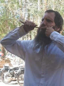 A Jewish Orthodox guy practicing blowing the shofar on a Leh street