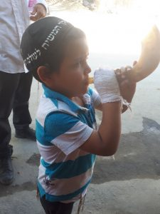 Orthodox kid blowing shofar on a Leh street
