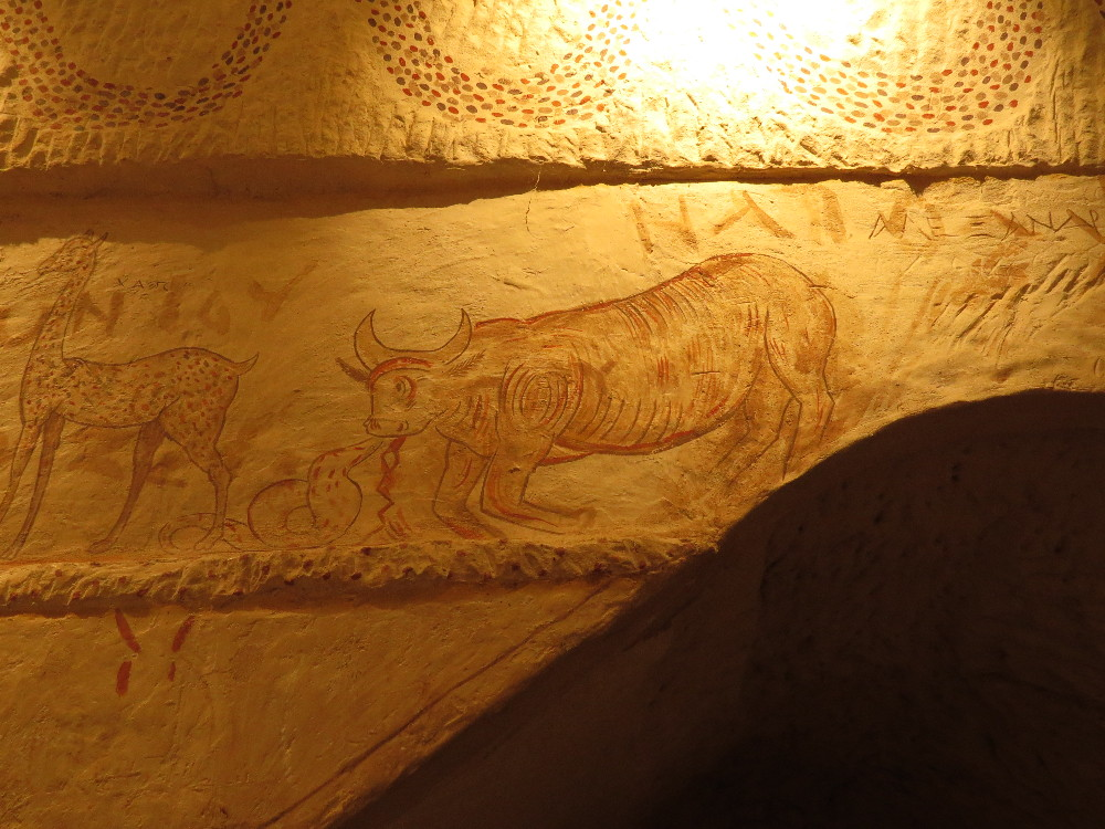 Bull fighting a snake, and giraffe. Apollophanes Cave