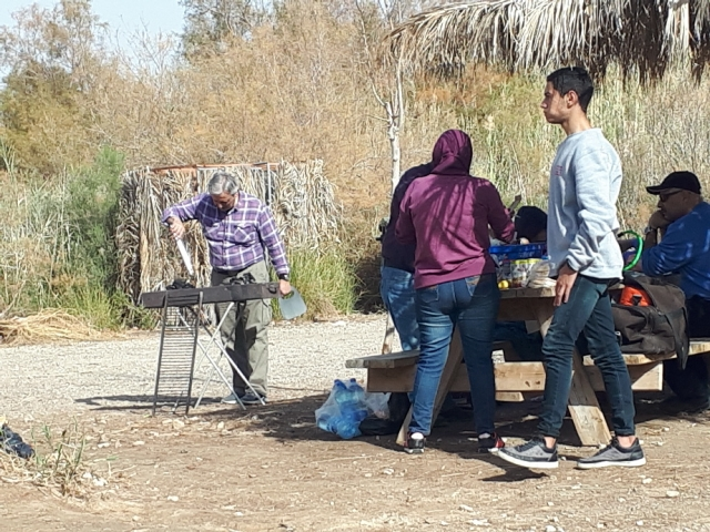Fanning the meat. arabs having a mangal at Einot Tzukim Nature Reserve