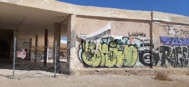 Graffity on abandoned British military base. Security road past Lido
