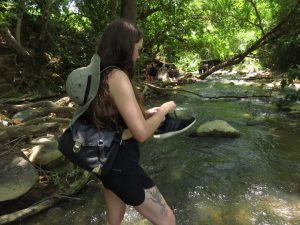 Ela taking off shoe in Snir Stream water walk