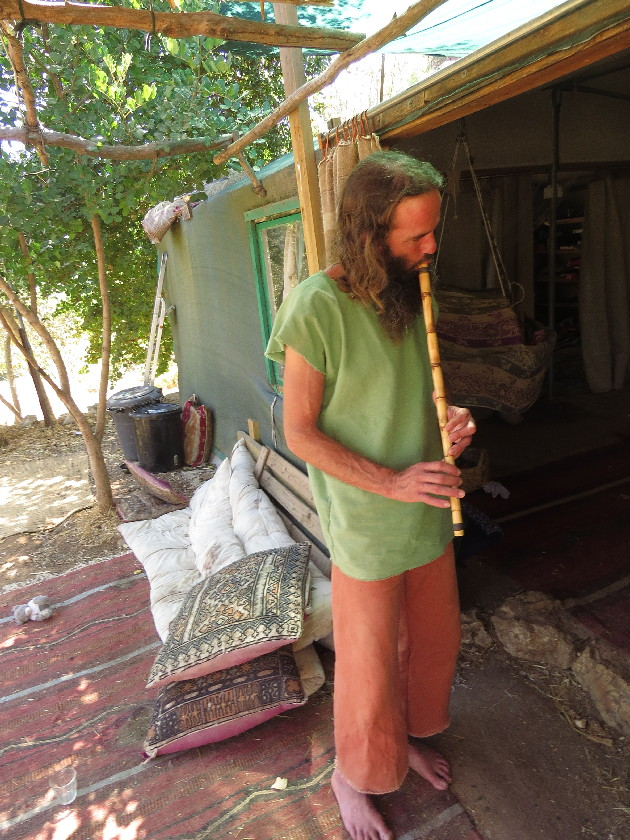 Yashar playing flute in front of tent-house. Ein Kerem