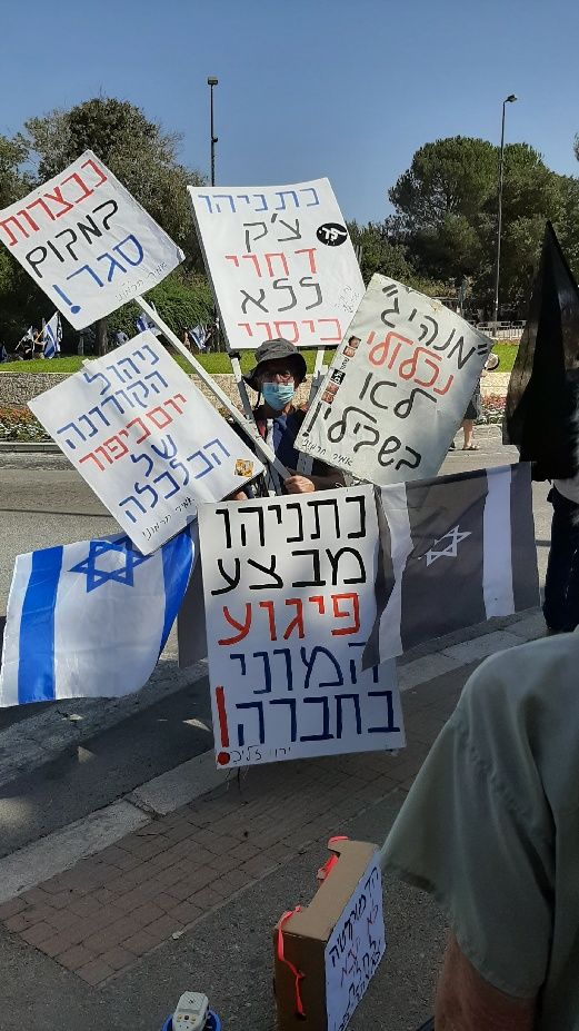 The man and his signs and the Knesset protest
