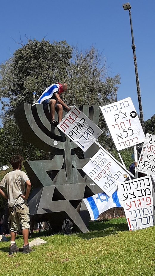 Multiple signs and one man. Here his signs are leaned against the Knesset Menorah